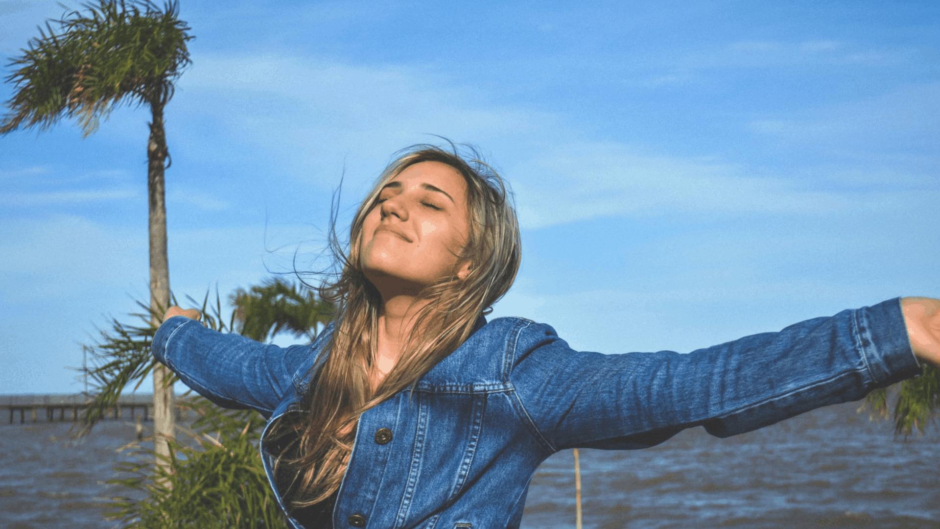 Glückliche Frau streckt die Arme nach links und rechts aus und genießt das Leben