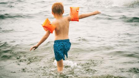 Kind geht mit Schwimmflügeln ins Meer