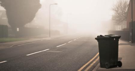 Ein Mülleimer der alleine auf einer Straße steht