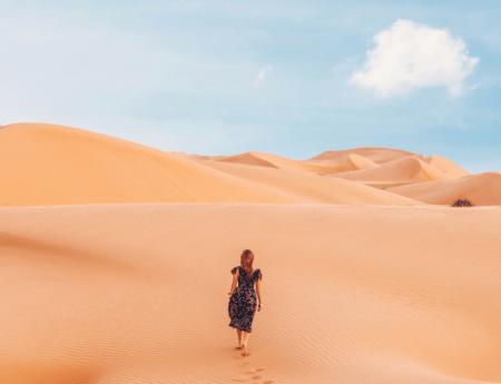 Frau steht in einer Wüste