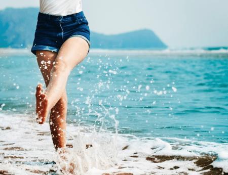 Halbe Frau mit Füßen im Meer auf einem Bein stehend