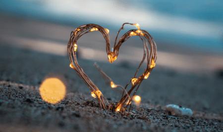 Selbstgebasteltes Herz steht am Rande des Meeres